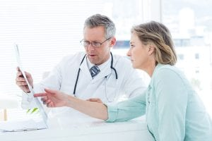 Doctor having conversation with his patient and holding xray in