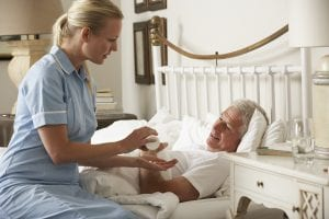 Nurse Giving Senior Male Medication In Bed At Home